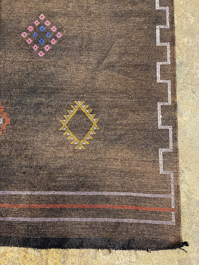 corner of brown sabra rug with colorful outline and designs