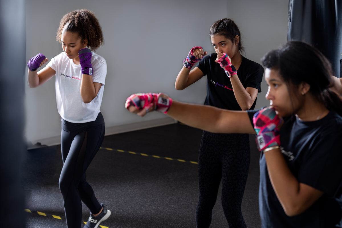 3 young women in a boxing stance wearing Girls Just Wanna Box cropped tshirts