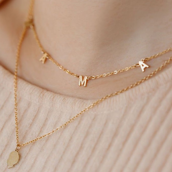 Close up image of layered necklaces, one is a gold kid silhouette necklace 18 inches and the short 16 inch necklace is a gold necklace that spells out MAMA