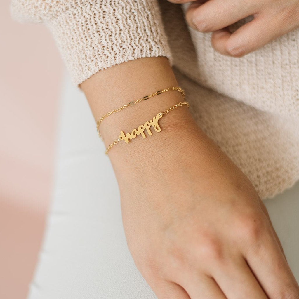 Woman wearing handmade gold bracelet and handmade custom handwriting cutout bracelet in gold