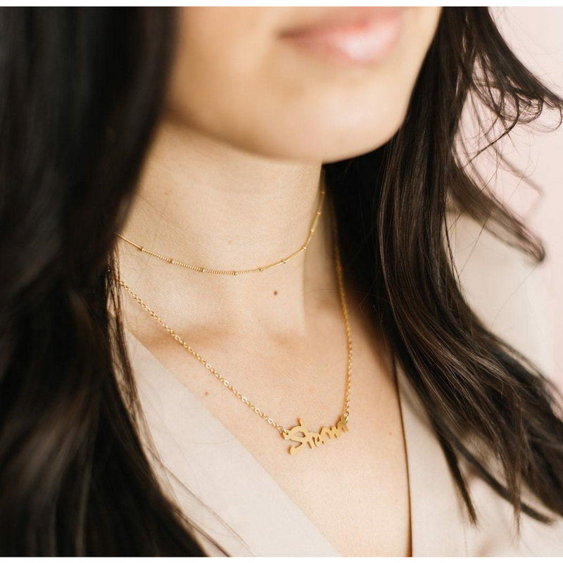 gold minimal choker necklace layered with a name necklace