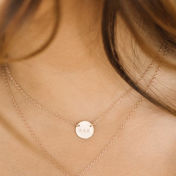 Woman wearing custom initial coin necklace and custom heart necklace
