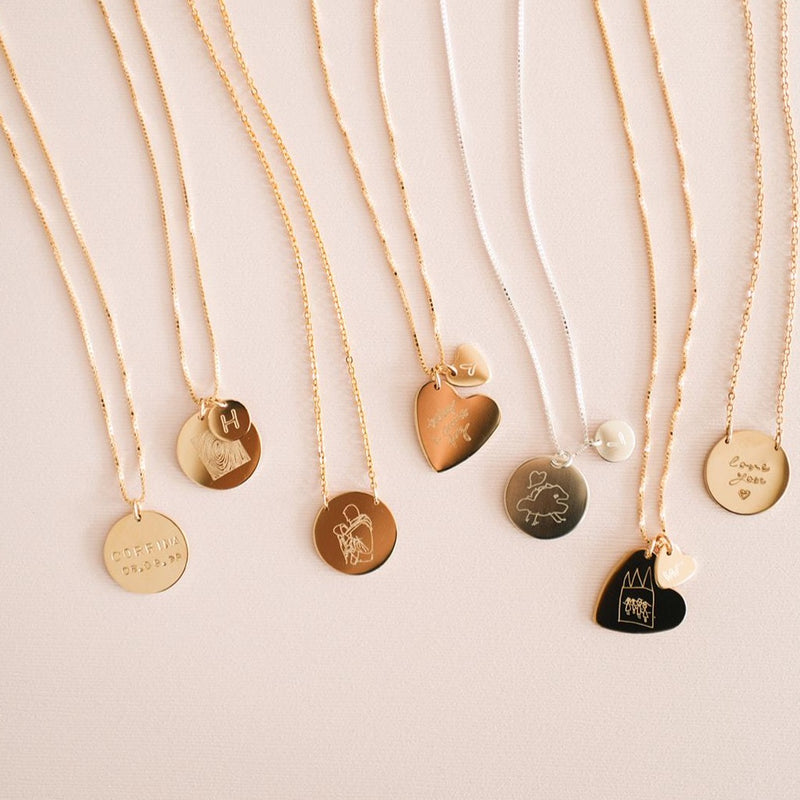 Variety of handmade custom drawing necklaces with coin and heart shaped pendants. Available in gold, rose gold and sterling silver