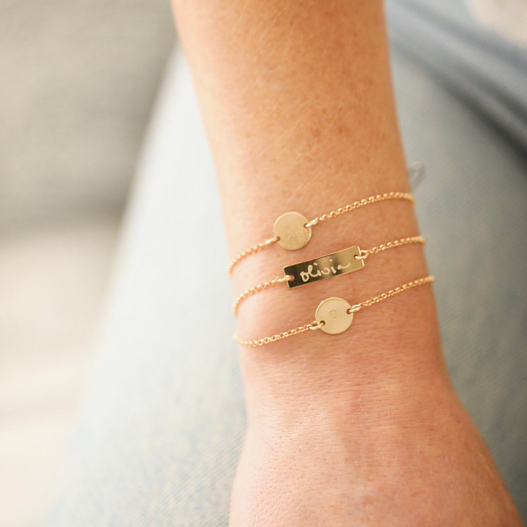 Two custom handmade initial coin bracelets in gold and one handmade custom bar bracelet in gold