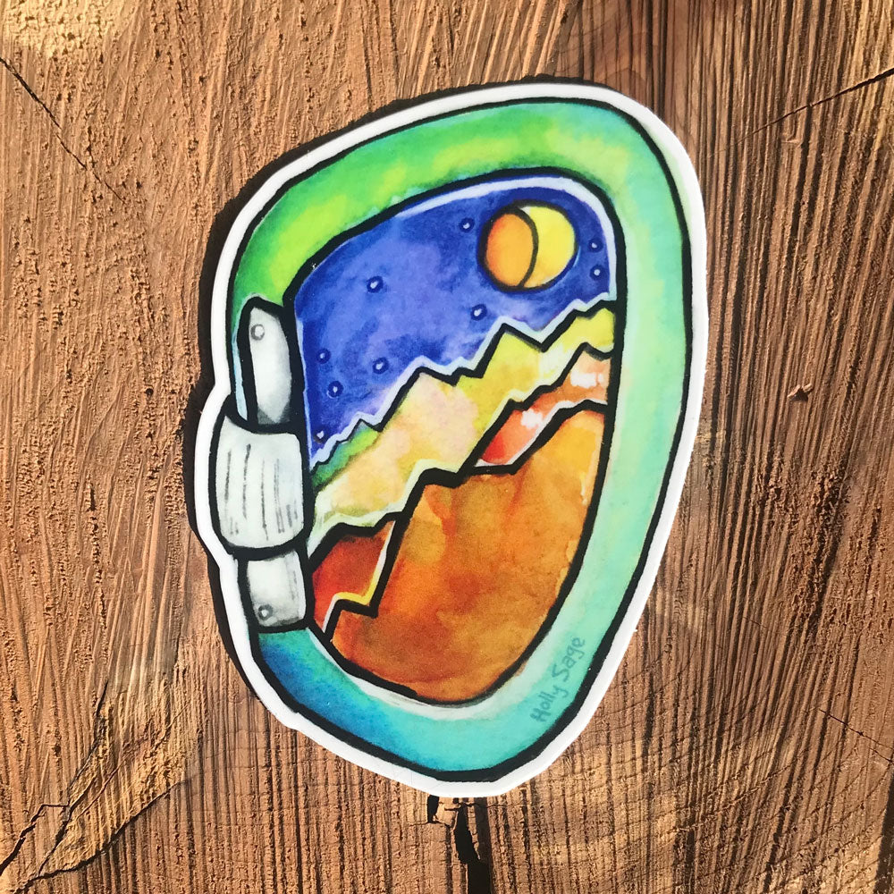 A carabiner sticker with rugged mountains inside