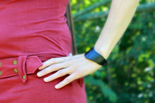 model with hand on hip wearing black half cuff bracelet