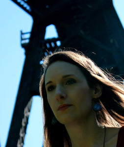 model in front of bridge wearing rose gold and black earrings