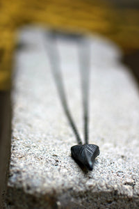 close up of triangle pendant of the gunmetal layering necklace