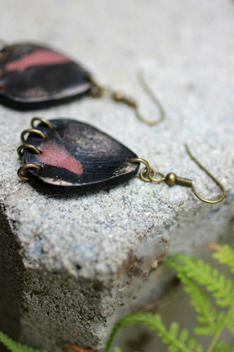 black and rose gold earrings with jump rings as focal point lying on stone
