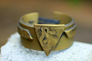 gold triangle cuff bracelet on stone