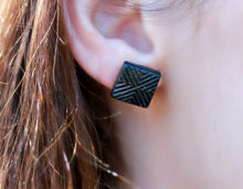model wearing black square stud earring without the jacket