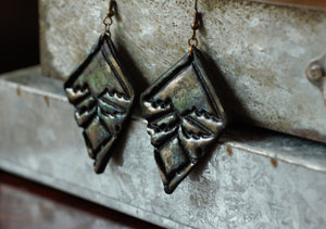 Ornate black bold earrings hung on steel drawer