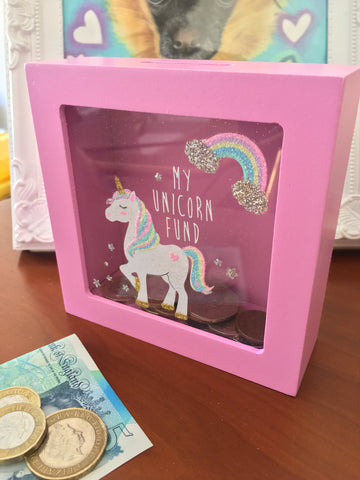 "Pink wooden little girl's money box with ""My Unicorn Fund"" text and pastel rainbow and unicorn figure on front. Glass front so you can see contents."