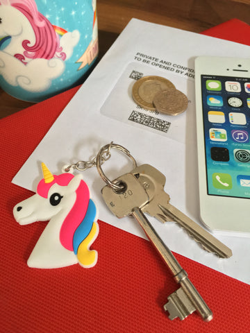 White silicone rubber unicorn head keyring or bag zipper charm with cute, bright pastel rainbow mane.