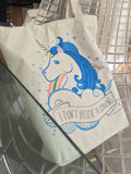 """I Don't Believe In Humans"" white cotton tote bag with zip top and blue unicorn head design"