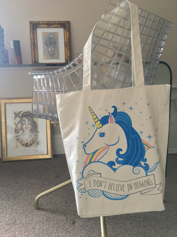 "Unicorn cotton tote bag with zip fastening and ""I Don't Believe In Humans"" text"