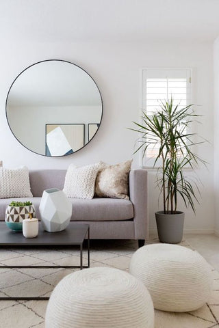 Neutral tones living space with round mirror and plant