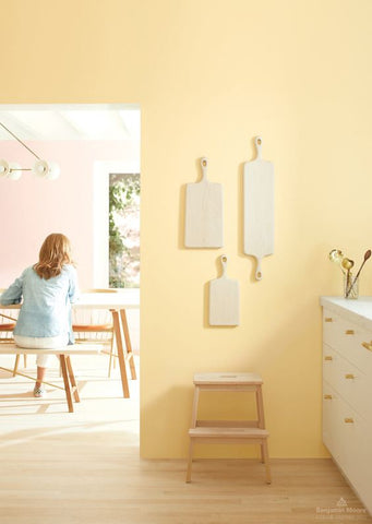 Pale yellow kitchen with wooden chopping boards on wall