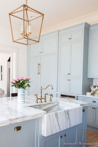 Light blue kitchen design with gold lampshade