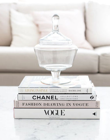 Designers books on a coffee table with a vase on top