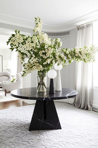 Flowers in a vase on a table in a hallway
