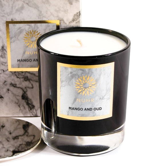 Mango and Oud white wax candle in black glass jar container with silver lid next to it and marble print gift box at back