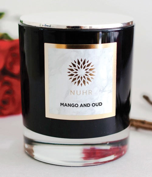 Mango and Oud white wax candle in black glass jar container with silver lid and red roses and branches at back