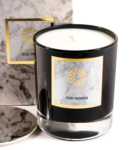 White wax Oud woods candle in black glass jar with silver lid to the side and white marble print gift box at the back