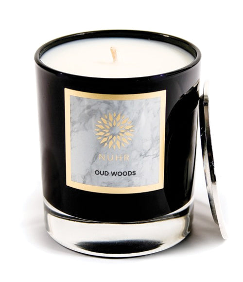 White wax Oud woods candle in black glass jar with silver lid leaning against candle
