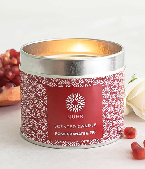 Lit Pomegranate and Fig candle with red wraparound label and pomegranate at back, arials at front