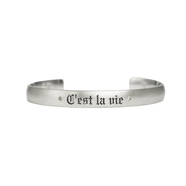 "Satin brushed sterling silver cuff bracelet with champagne diamonds next to custom engraving reading ""C'est la vie"" in fine Gothic letters"