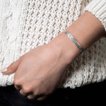 "Sterling silver cuff with ""Gratitude"" engraved on it pictured on a woman's wrist"