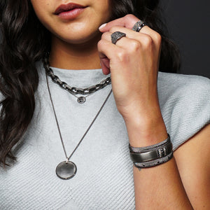 Closeup of a woman wearing three sterling silver layering necklaces and showing a stack of darkened silver cuffs on her wrist
