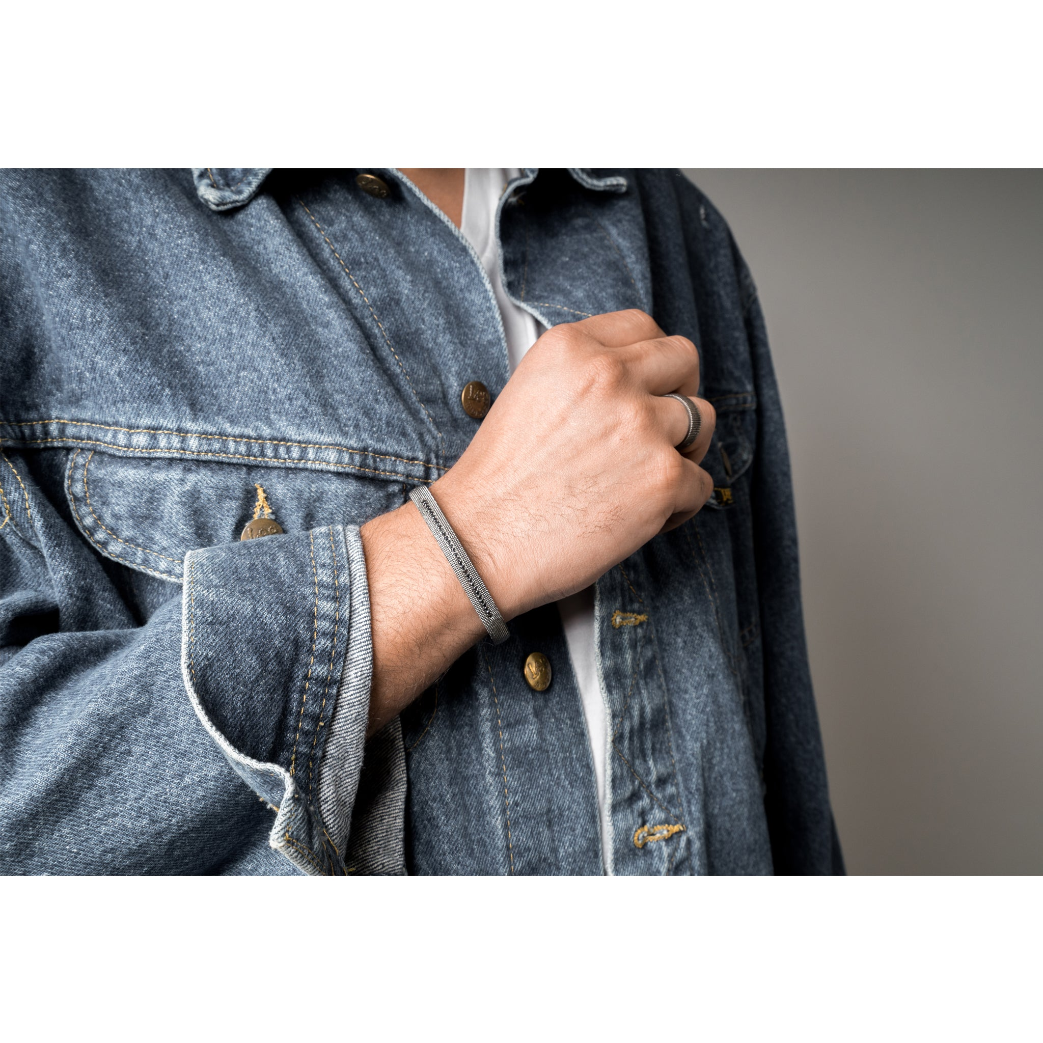 Closeup of a man in a denim jacket holding up his wrist to show a men's bracelet- a textured sterling silver cuff with black diamonds being worn