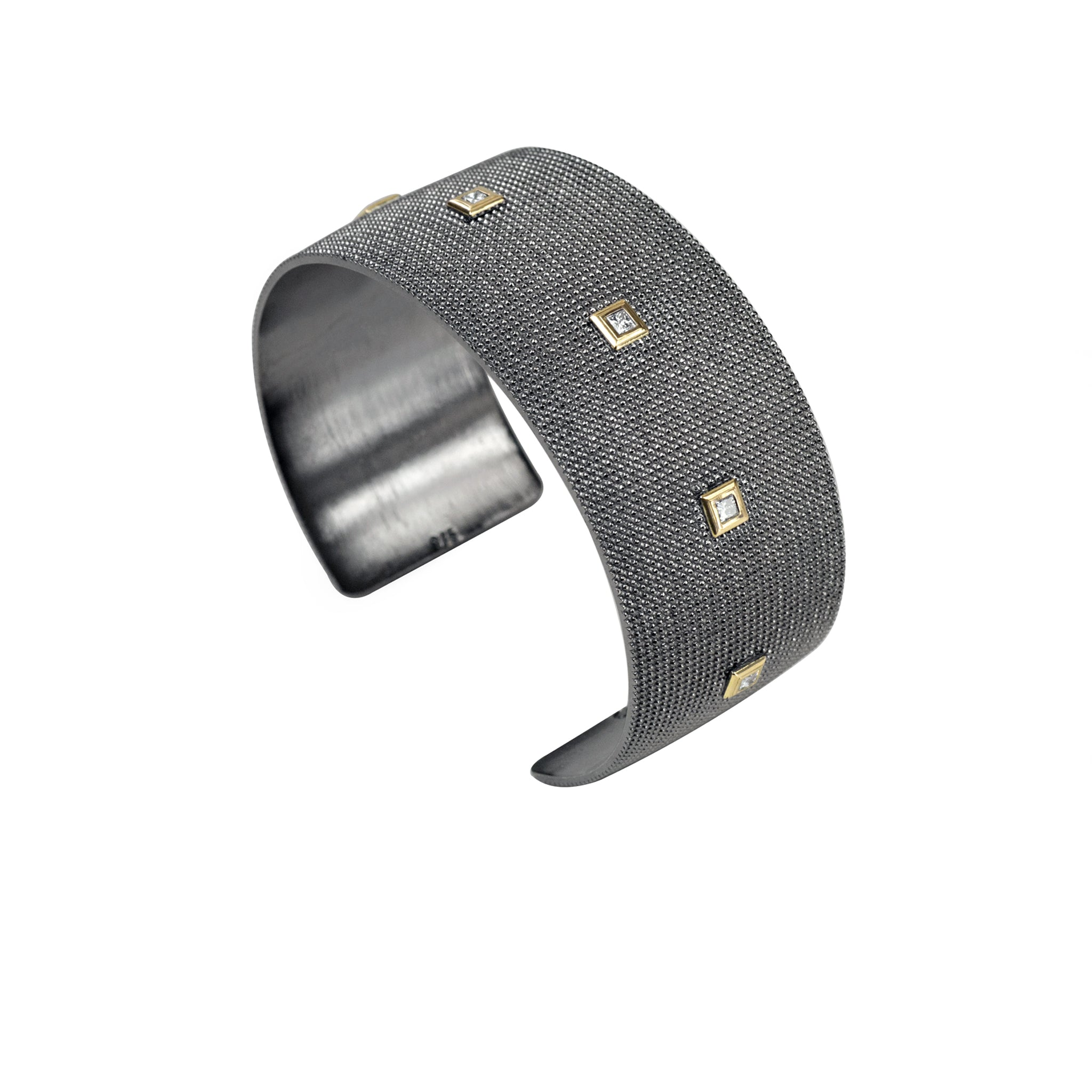 Wide textured sterling silver cuff with 14K yellow gold bezeled white diamonds from an angle