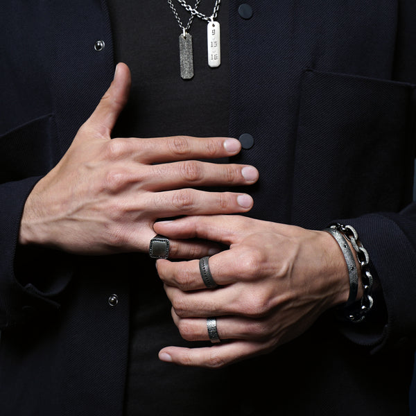 Sterling silver and black diamond men's jewelry styled on a male model including men's chains, bar pendants, silver men's rings, men's bracelets, and a men's link bracelet