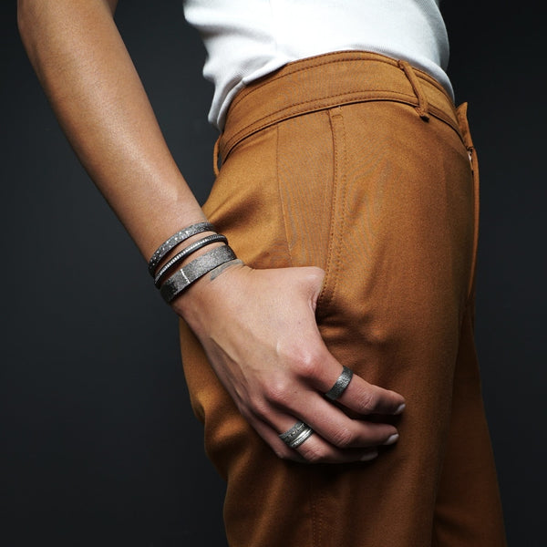 Model wearing three sterling silver and diamond cuff bracelets and silver rings styled