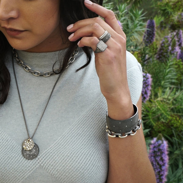 Sterling silver and diamond jewelry styled on a model including pendants, link necklaces, link bracelet and cuff, signet rings, and stacking bands.