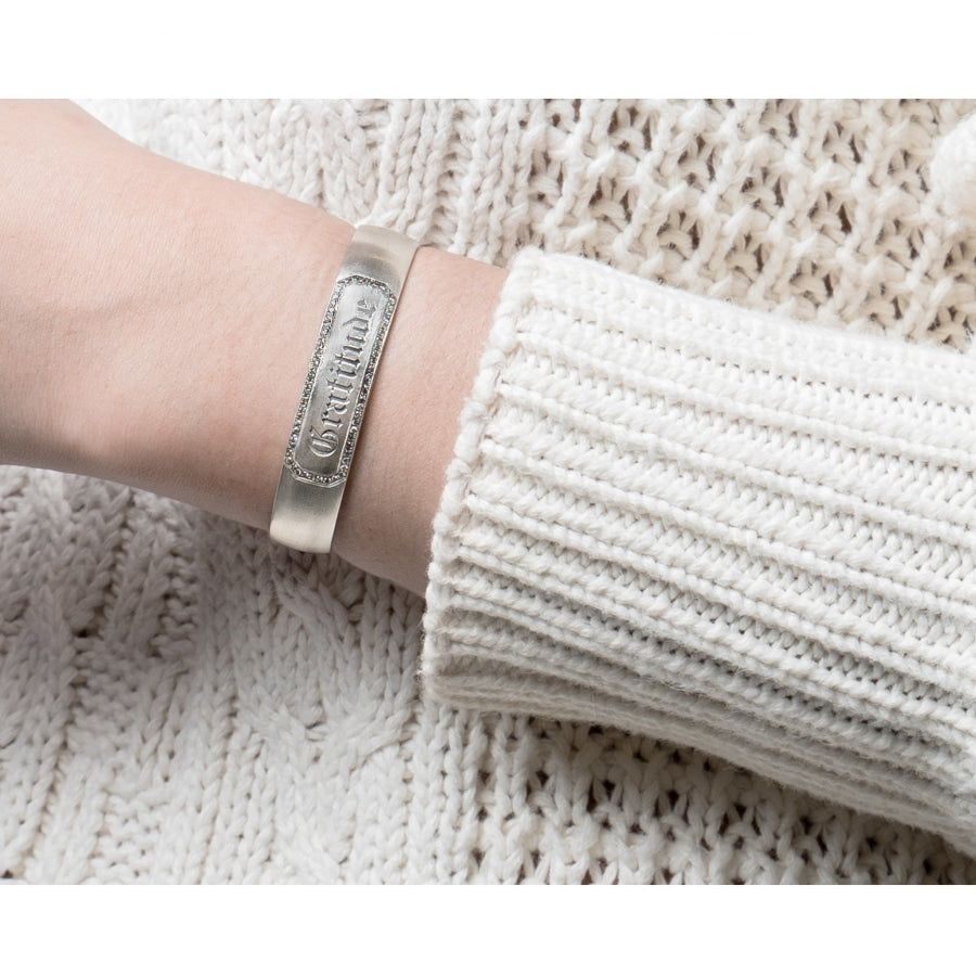 "woman wearing wyatt cuff with champagne diamonds and ""gratitude"" engraved on her sterling silver bracelet"