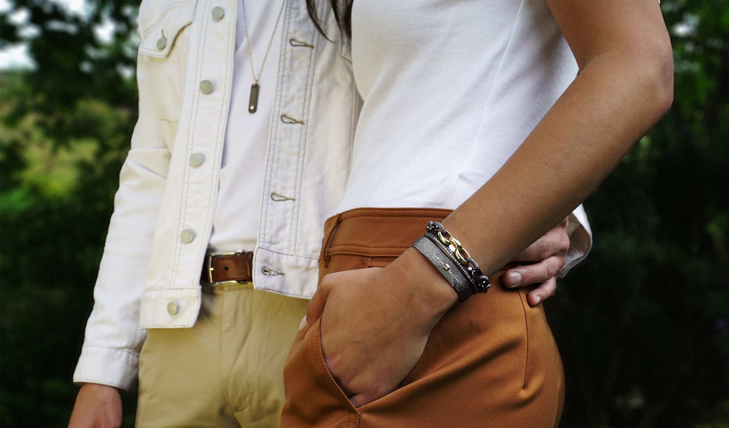 Closeup of a man and woman wearing sterling silver and gold jewelry. On the left he wears a bar pendant and has his hand around her waist. On the right, her hand is in her pocket displaying a cuff and link bracelet on that wrist.
