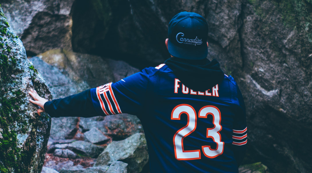 man wearing Kyle Fuller Broncos jersey and Cannadips CBD logo cap faces away from the camera