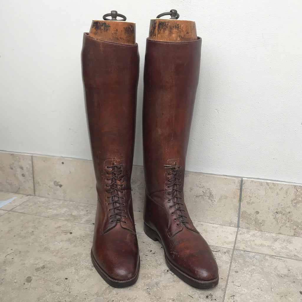 Pair of Antique British Army Officers Cavalry Boots in wonderful condition. Finished in brown leather with laces to the bottom section of the boot and leather soles. Each boot has its original wooden stave with the Faulkner & Son makers mark and topped off with a sturdy brass pull ring - SHOP NOW - www.intovintage.co.uk