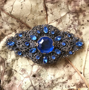 Excellent quality Edwardian Brooch with intricate design detail. Numerous faceted glass sapphires surrounding one larger blue glass gem. - SHOP NOW -  www.intovintage.co.uk