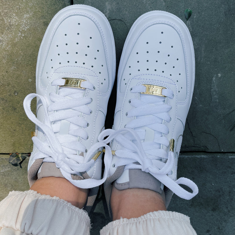 Pair of white Nike Air Force 1 sneakers with gold AF1 lace plate, gold aglets, and beige tongue tag, sock lining