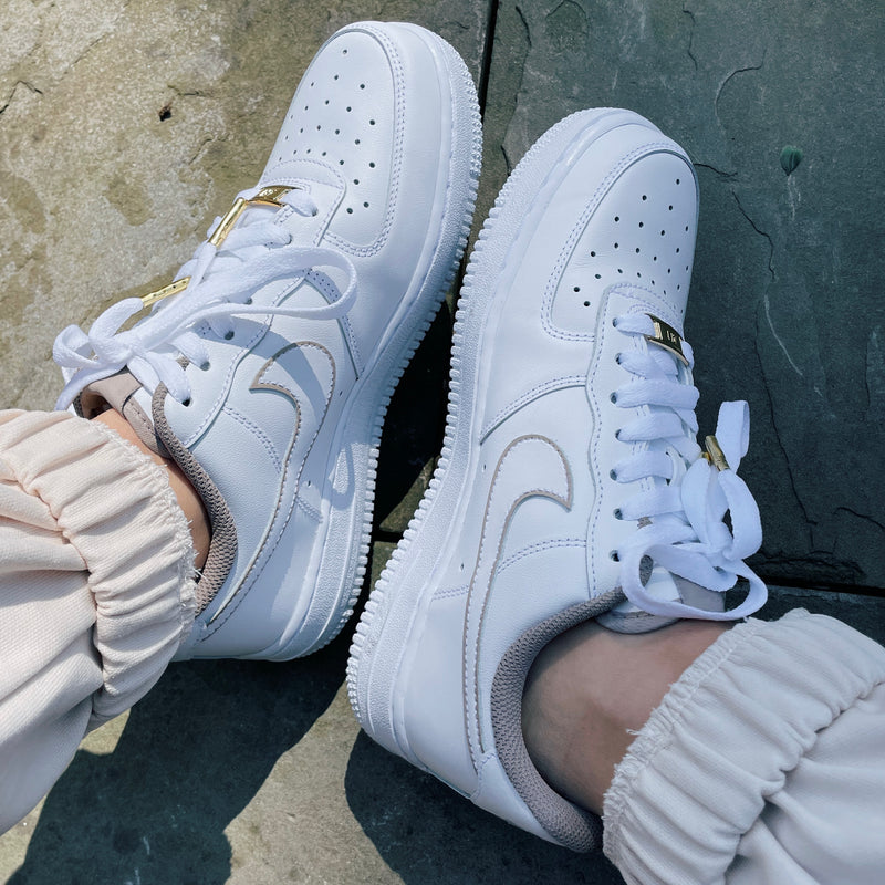 Pair of white Nike Air Force 1 sneakers with gold AF1 lace plate, gold aglets, and beige tongue tag, sock lining, and outline of swooshes