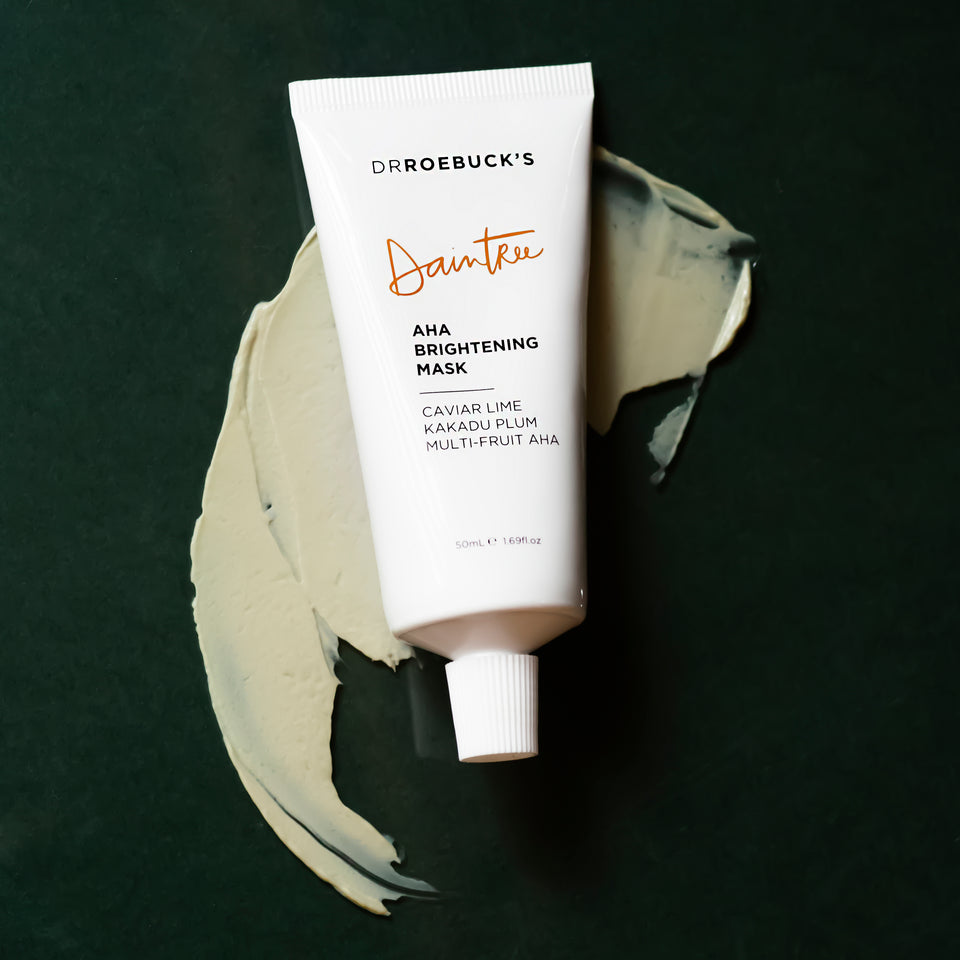 Dr Roebuck's Daintree AHA brightening mask tube with product shown on dark background