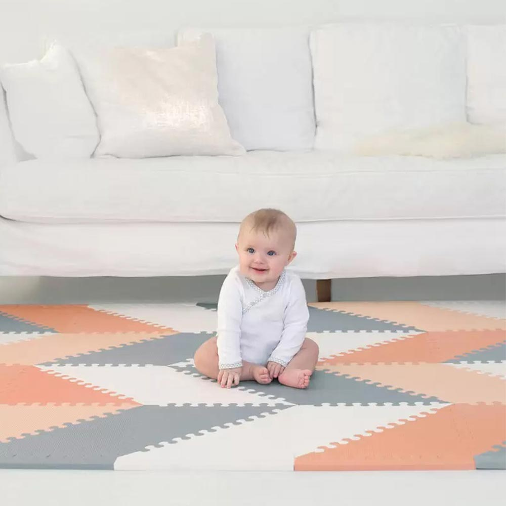 A baby sitting on their playspot made with Skip Hop's Geo Foam in grey, white and peach triangles.