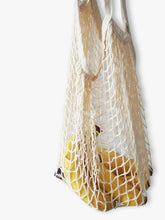 Reusable shopping bag made from organic cotton hanging with bananas in