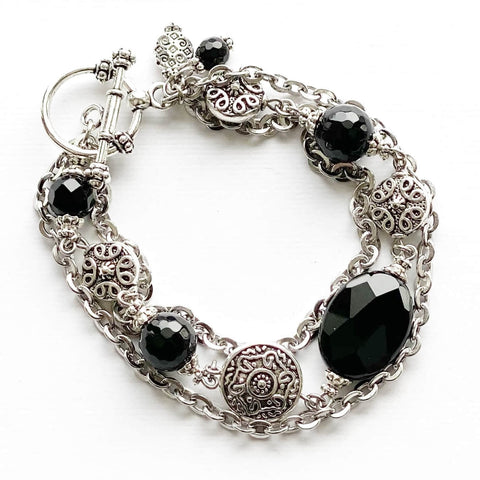 Stainless steel chain and black onyx bracelet with silver pewter beads. It closes with a pewter toggle clasp.