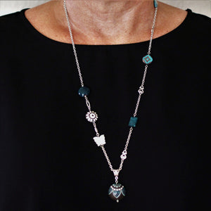 This long pendant necklace uses stainless steel chain. The pendant is a round brown design. This womens necklace is accented with a white butterfly and apatite stone.